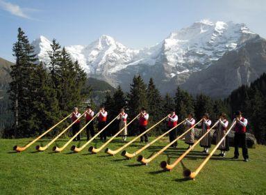 Alpesi kürtön játszó svájciak népviseletben.